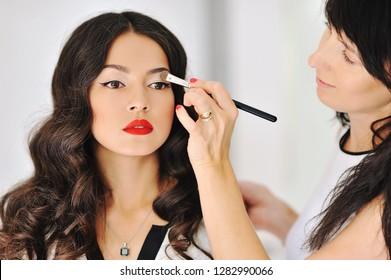 Woman applying makeup by professional makeup artist