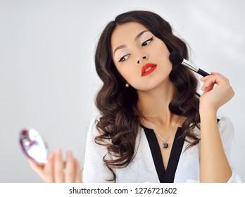 Woman applying makeup - close up portrait