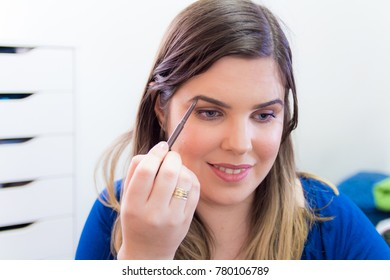 Woman applying makeup in her bedroom. She is smiling.