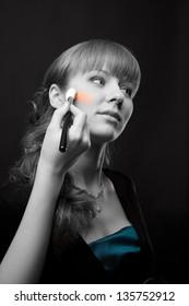 Woman applying makeup onto beautiful performer's face