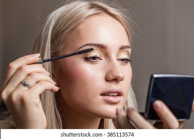 woman applying makeup using make up brush with mirror