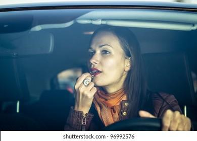 Woman applying makeup while driving