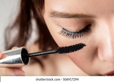 Woman applying mascara on eyelashes with makeup brush