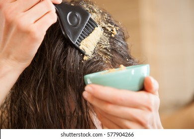Woman applying mask to hair roots to make them grow stronger and faster and to prevent hairloss