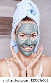 Woman applying mask moisturizing skin cream on face looking in bathroom mirror. Girl taking care of her complexion layering moisturizer. Skincare spa treatment