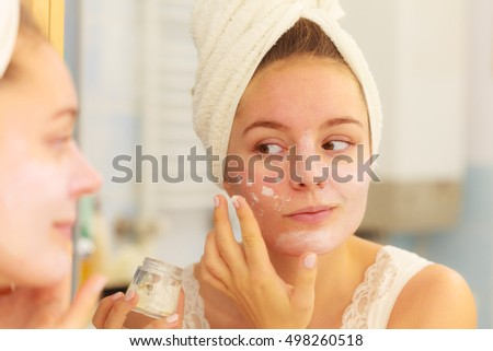 Woman applying mask moisturizing skin cream on face looking in bathroom mirror. Girl taking care of her complexion layering moisturizer. Skincare spa treatment.