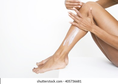 A woman applying moisturiser to her legs