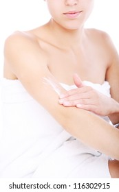 Woman applying moisturizer cream on the hand over white background