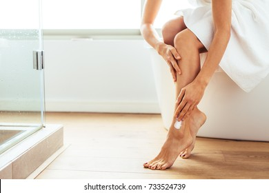 Woman applying moisturizer to her legs after bath. Woman in bath towel sitting on bathtub in bathroom.