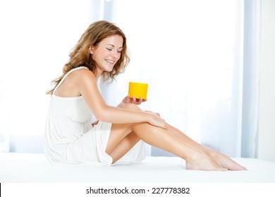 Woman applying moisturizer on her legs.