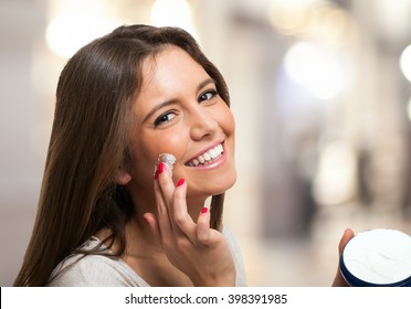 Woman applying a moisturizer on her face