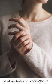 Woman applying moisturizing cream on hands. She wear roze sweater