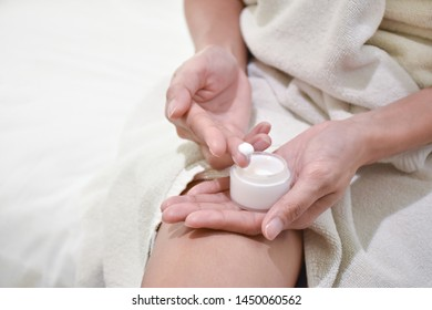 Woman applying moisturizing cream/lotion on hands, beauty concept.