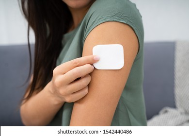 Woman Applying Patch On Her Arm At Home