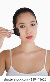 Woman applying powder to face with large makeup brush on white background