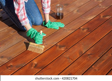 Woman applying protective varnish or wood oil on a patio wooden floor, house maintenance concept. Before and after effect