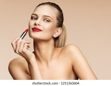 Woman applying red lipstick. Photo of attractive girl with perfect makeup on beige background. Beauty concept
