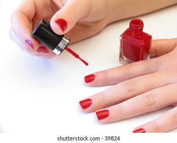 woman applying red nail polish on white background