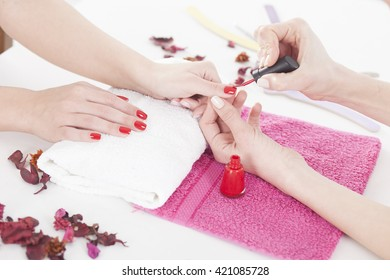 Woman applying red nail varnish to finger nails. Woman is having a manicure bt beautician