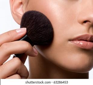 woman applying rough on cheek - macro shot