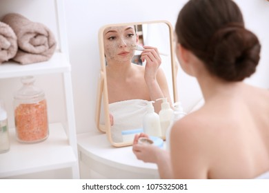 Woman applying scrub onto face in front of mirror at home