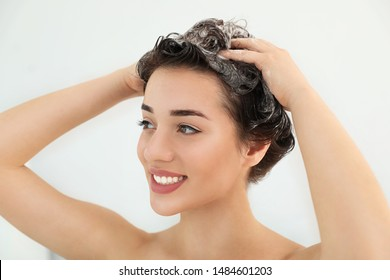 Woman applying shampoo onto her hair against light background