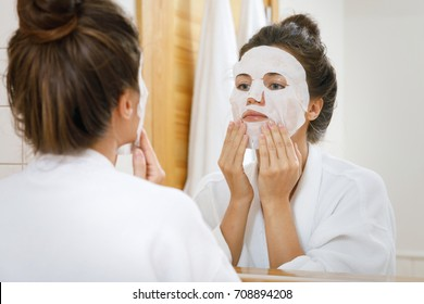 Woman is applying sheet mask on her face in the bathroom