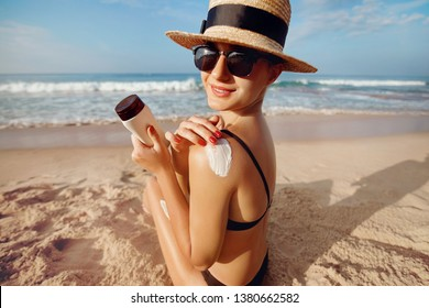 Woman applying sun cream on  tanned  shoulder. Skincare. Body Sun protection suncream. Bikini hat woman using moisturizing sunscreen lotion on back