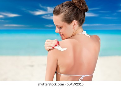 A woman is applying sunblock on her back. Close-up