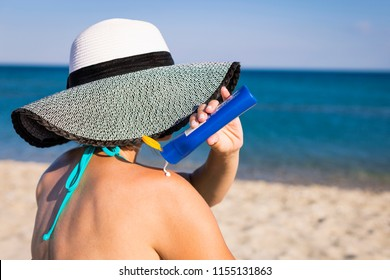 Woman applying sunscreen cream on her body outdoors under sunshine on beautiful summer day.. Skincare. Body Sun protection suncream.  Sunscreen sunblock.