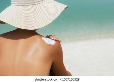 Woman applying sunscreen creme on  tanned  shoulder. Skincare. Body Sun protection suncream. Bikini hat woman applying moisturizing sunscreen lotion on back.