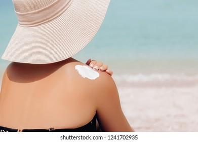 Woman applying sunscreen creme on  tanned  shoulder. Skincare. Sun protection sun cream. Bikini hat woman applying sunscreen lotion on back