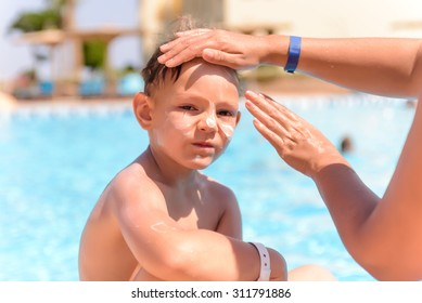 Woman applying sunscreen to the face of her young son as he sits waiting to go swimming alongside a swimming pool, close up of him looking at the camera