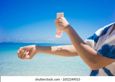 Woman applying sunscreen on her hands from a bottle on the beach with the sea in the background. SPF sunblock protection concept.selective focus
