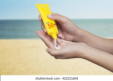 woman applying sunscreen on her hand with sea background. SPF sunblock protection concept. Travel vacation