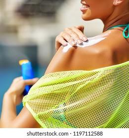 Woman applying sunscreen on shoulder