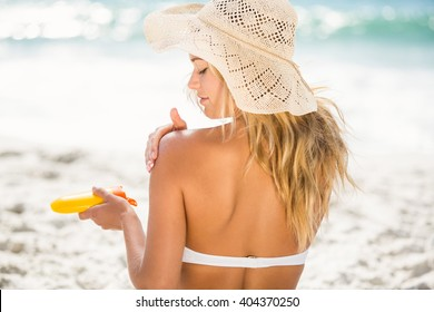 Woman applying sunscreen on a sunny day