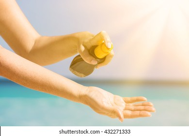 Woman applying sunscreen protection cream against turquoise caribbean sea water and blue sky. Tropical summer vacation concept