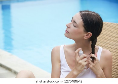 Woman applying sunscreen spray, hair care protection during summer vacation