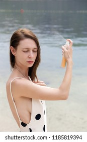 Woman applying sunscreen spray on the beach, hair care protection concept