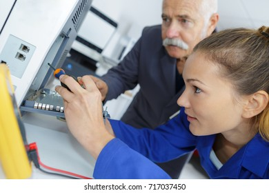 woman apprentice computer repairer monitored by teacher