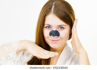 Woman appying clear-up strips on nose, using pore cleansing textile mask for blackheads. Girl taking care of skin complexion. Beauty treatment. Skincare.