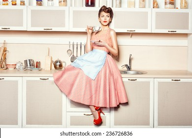 Woman in an apron in the kitchen drinking from a cup sitting on the table.
