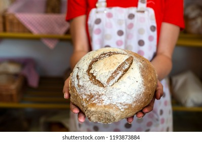 Woman in apron shows bread in a bakery.