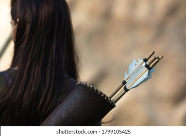 Woman archer standing with her back with quiver for arrows on blurred background
