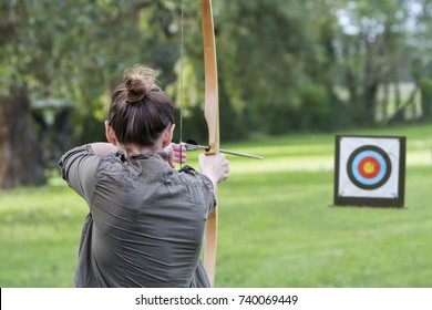 Woman archer to use a bow and arrow and shoot at a target