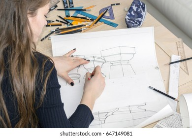 Woman architect draws a plan, design, geometric shapes by pencil on large sheet of paper at office desk