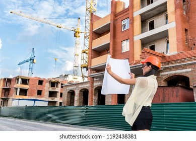 Woman architect in orange helmet with drawing near construction site