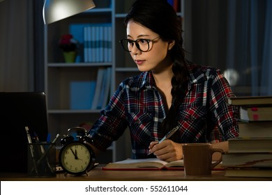 Woman architect working at construction project late at home. Young female executive having deadline. mixed race asian chinese model.