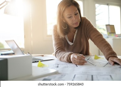 Woman architect working on blueprints in office